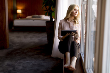 View at young businesswoman sitting by the window and using digital tablet