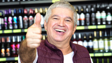 Senior Man Satisfied with Thumbs Up in Supermarket