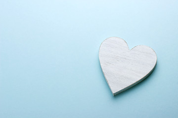 White wooden heart on blue cardboard background.