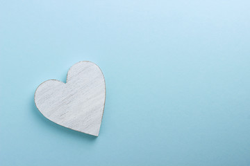 White wooden heart on blue cardboard background.