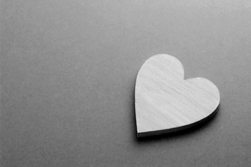 White wooden heart on black and white cardboard background.
