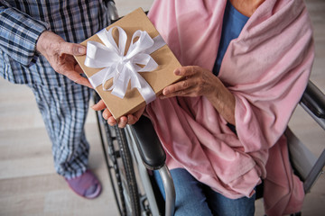 Top view close up of male and female hands holding the box with bow. Woman is sitting in invalid chair and man is standing near her