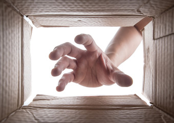 Man is stretching hand into cardboard box,View from the box