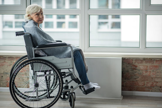 Upset mature woman looking at camera with sad look. She is sitting in wheelchair in room wrapped in a blanket. Copy space in right side