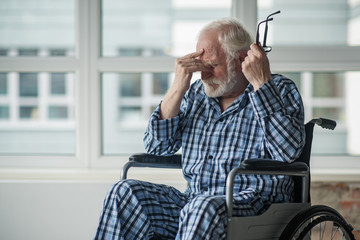 Sad senior male sitting in wheelchair in room with hopeless face. He is holding his eyeglasses and touching the bridge of his nose