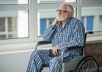 Moody old man holding the book in his hands and sitting in invalid chair near the window. He is feeling upset and alone at home
