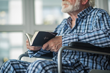 Old man holding the Bible in his hands and sitting in invalid chair. He is wearing pajamas and spending time at home. Hope and faith concept
