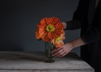 Frau dekoriert Blumen in einer Glasvase auf einem Tisch