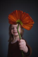 Kleines Mädchen hält eine große orange farbene Blume in der Hand