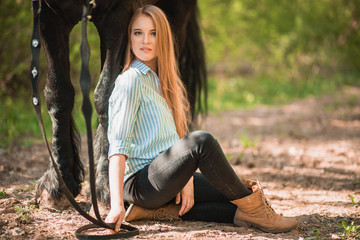 Handsome slim woman sitting on the ground with brown horse near her.