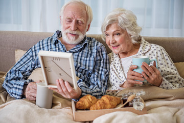 Tranquil old man holding frame with photo. Cheerful married couple looking at photograph with serene smile
