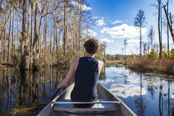 POV shot of canoe with teen paddling in Okefenokee swamp.