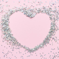 Heart border frame made of glitter on a pale pink pastel backgro