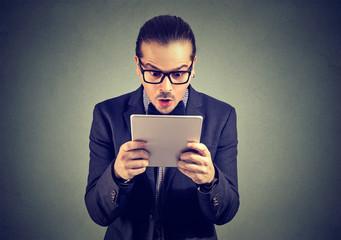 Shocked man staring at tablet