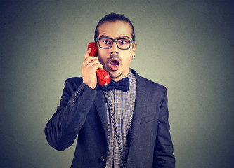 Businessman looking shocked while speaking on phone
