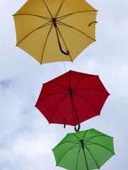 Bunte Regenschirme fliegen an einem windigen Sommertag durch die Luft