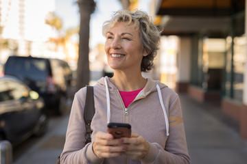 Mature caucasian woman walking texting cell phone