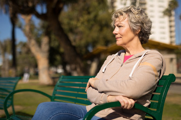 Mature caucasian woman sitting on a park bench