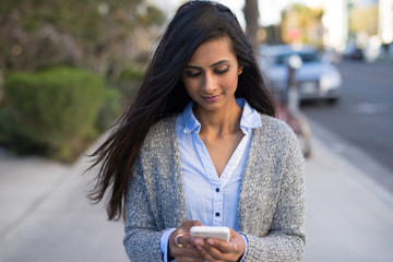 Young Indian woman walking street texting on cell phone