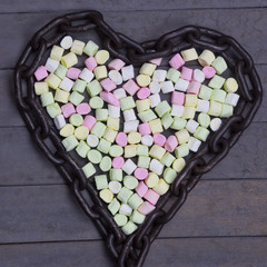 Multi colored Tasty Marshmallows chained in Shape of Heart. Flat Lay studio image. Food Concept. Love Background.