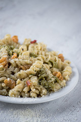 pasta salad with herbs and olive oil on white plate in bright setting