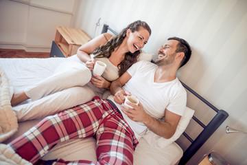 Happy couple in love having romantic moment in bedroom.