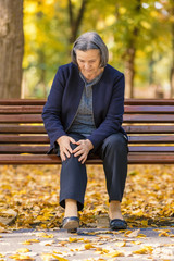 Senior woman having knee pain sitting on bench in park