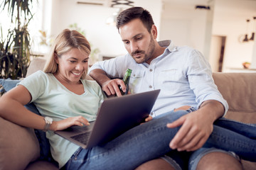 Young couple sitting in the living room and using laptop.