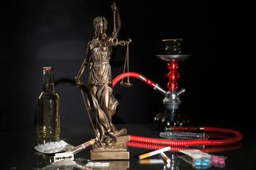Legale und illegale Rauschmittel – Justitia Statue inmitten von Rauschmitteln vor schwarzem Hintergrund