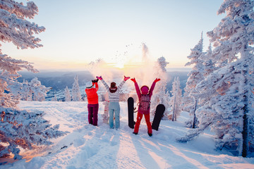 Happy team of snowboarders having fun tossing snow and fun. Wall mural