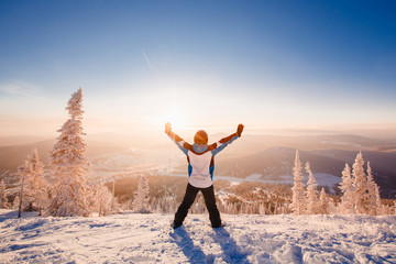 Male skier raises his hands up against the background of snowy mountains, forests, sunrise. Concept victory, freedom, lifestyle.