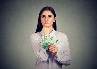 Woman with money deciding on spending