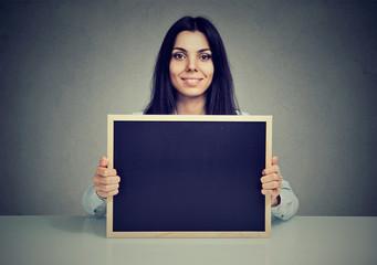 Content woman showing blank blackboard