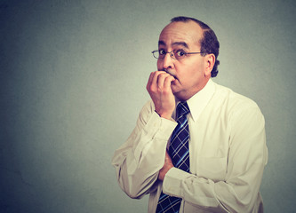 Anxious male worker biting nails