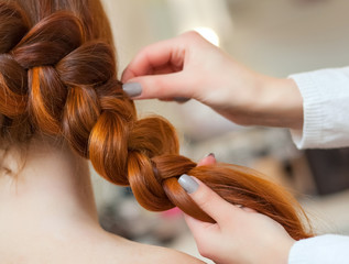 Beautiful girl with long red hair, hairdresser weaves a braid, in a beauty salon. Professional hair care and creating hairstyles.