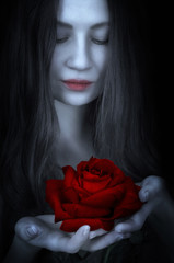 Beautiful girl holds a rose in hand. Focus on rose. Gothic concept.