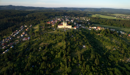 """Aerial view on Pilgrimage Church of the Visitation of the Virgin Mary - pilgrimage site of European significance """"The Holy Hill"""", from-afar visible silhouette of basilica minor lit by setting sun."""