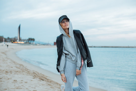Happy and natural beauty young pretty and attractive woman or teenager wears grey hoodie and sweatpants during workout at beach seaside laughs naturally to camera, during fashion photoshoot influencer