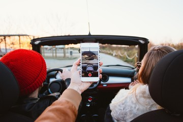POV of backseat travelling passenger making video photo or selfie on smartphone front phone camera inside of cabriolet convertible car at summer sunset, hang out with friends at travel destination