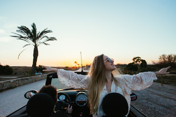 Excited and happy young female traveller or tourist enjoys warmth of summer inside rental convertible or cabriolet car on warm sunny day, palm trees aside road of holiday destination