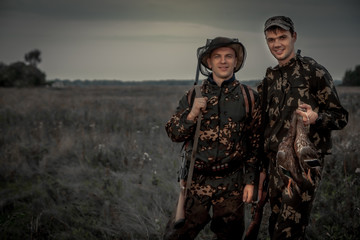 Foto op Aluminium Jacht Hunters men with trophy in rural field during hunting period at dusk
