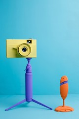 Bright retro vintage camera and orange web-camera on tripod on blue background, copy space. Multimedia, broadcasting, photography, vlog, blogging, art concept