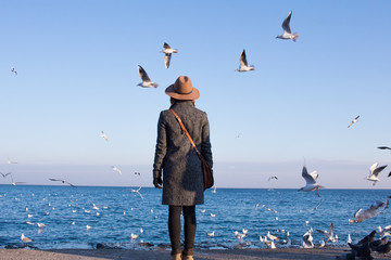 Young woman in hat stand on autumn beach n sunny day and watching seagulls