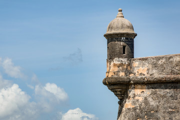 The outer tower and wall with sentry box of San Felipe del Morro fort in old San Juan in Puerto Rico, USA against the blue sky with clouds and copy space
