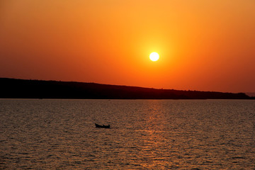 A sunset with the silhouette of a little local fisher boat on Lake Victoria with a rising hill on the background. Lake Victoria is the border of Tanzania, Kenya and Uganda, located in East Africa. Wall mural