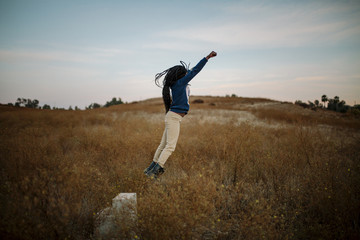 Side view of girl jumping on grassy field against sky