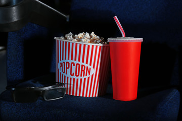Bucket with tasty popcorn and cola on chair in cinema