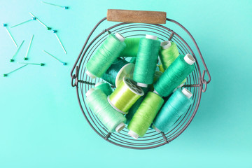 Metal basket with sewing threads on color background, top view
