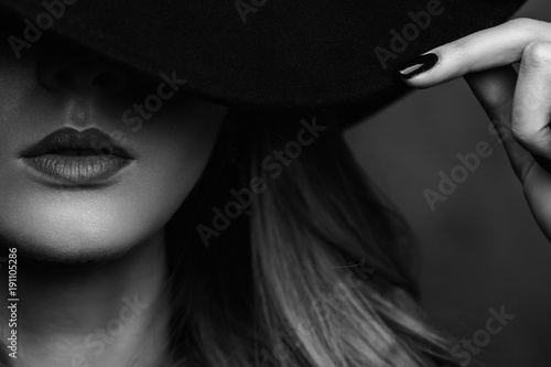 e3b46fd5f43 Beautiful young mysterious blond girl in black hat and black jacket on gray  background. Eyes are covered with a hat. Manicure - long red nails