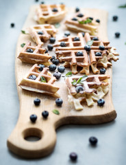 Traditional homemade belgian waffles with fresh ripe berries blueberry on wooden serving board over gray background.